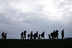 Silhouettes of migrants against a grey sky.